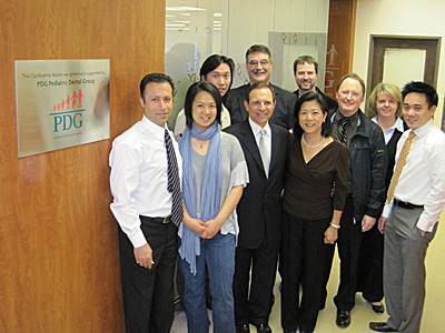 The Pediatric Dental Group outside the PDG Conference Room. Front row, from left to right: Drs. Reza Nouri, Louisa Leung, Richard Kramer, Anabel Chan. Back row, from left to right: Drs. Edward Chin, Donald Scheideman, Todd Moore, Donal Flanagan, Ms. Pam Waller, Dr. Christian Wong. Missing: Dr. David Kennedy.