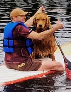 photo of Dr. Dale Henry sitting on an orange paddleboard with his golden retriever dog. He is wearing a blue life jacket.
